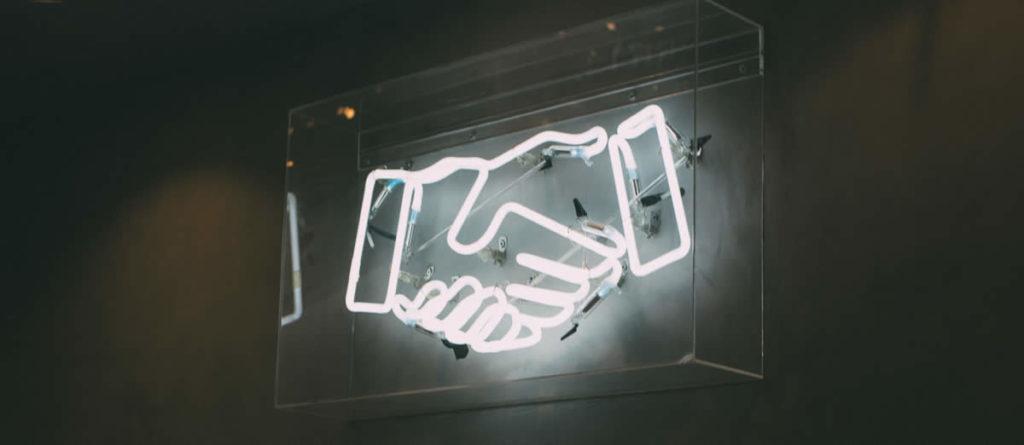Conexão com potenciais clientes no Linkedin, representada por duas mãos se cumprimentando.